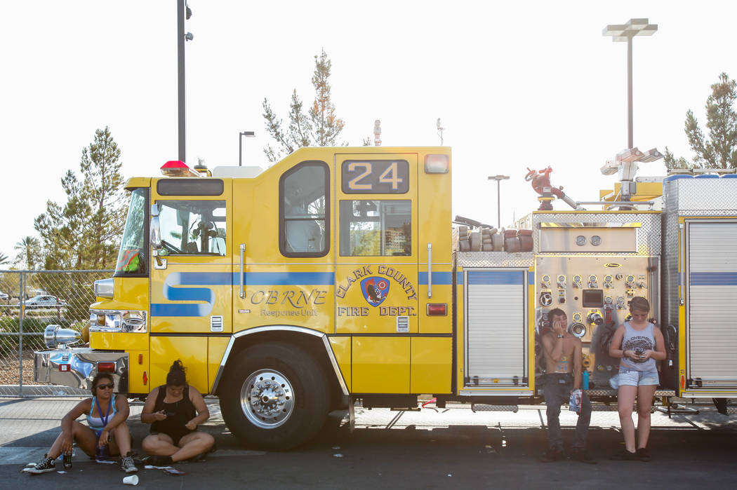 Warped Tour fans catch a break from the heat in the shade of a fire truck at the parking lot of the Silverton Casino in Las Vegas on Friday, June 28, 2013. (Chase Stevens/Las Vegas Review-Journal) ...