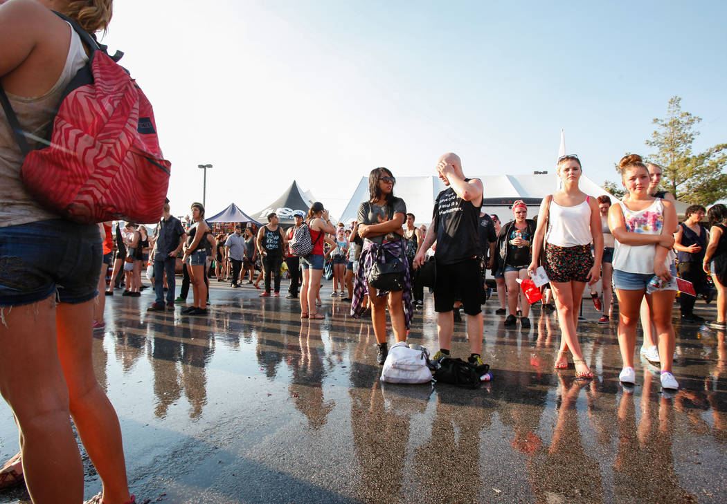 Fans stand near sprinkles spraying water while watching Memphis May Fire perform at the Kia Soul stage during the Warped Tour at the parking lot of the Silverton Casino in Las Vegas on Friday, Jun ...