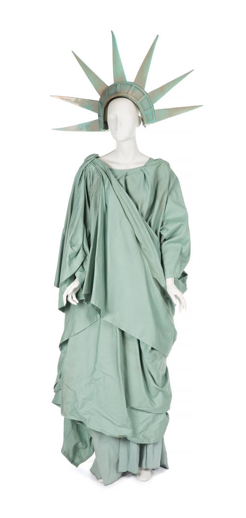 A multilayered floor-length green wrap dress designed by costume designer Erin Quigley in the style of the Statue of Liberty replete with a foam pointed crown with faux patination. Worn by Roseann ...