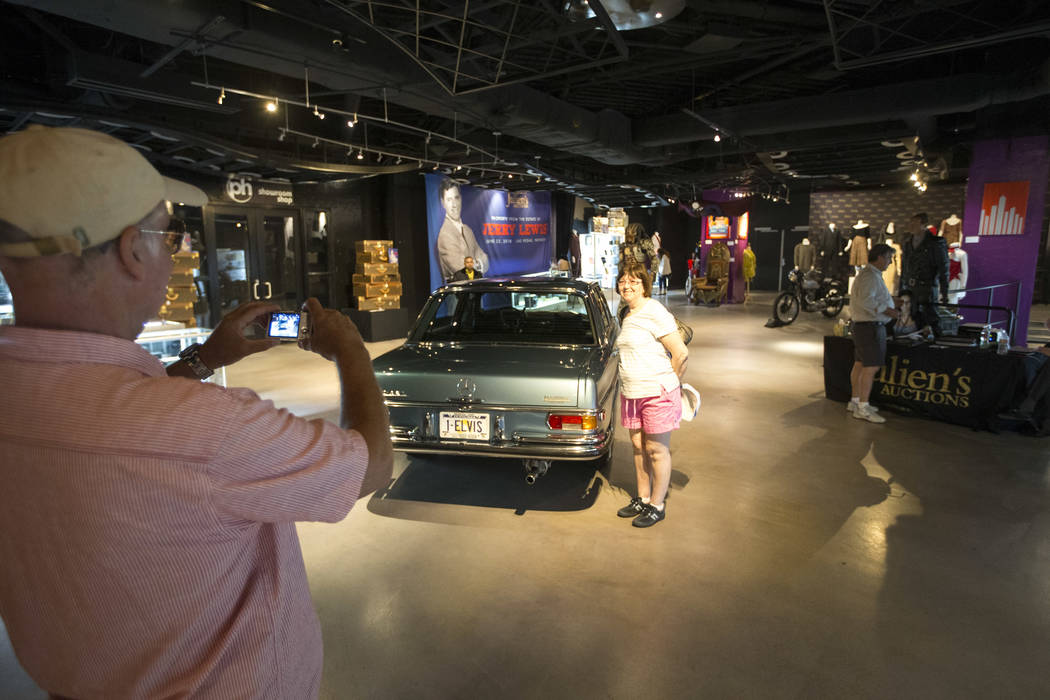People pose next to a 1970 Mercedes-Benz 280 SEL purchased new by Elvis Presley and retained until his death on display as part of Julian's Auctions Hollywood Legends collection at Planet Hollywoo ...