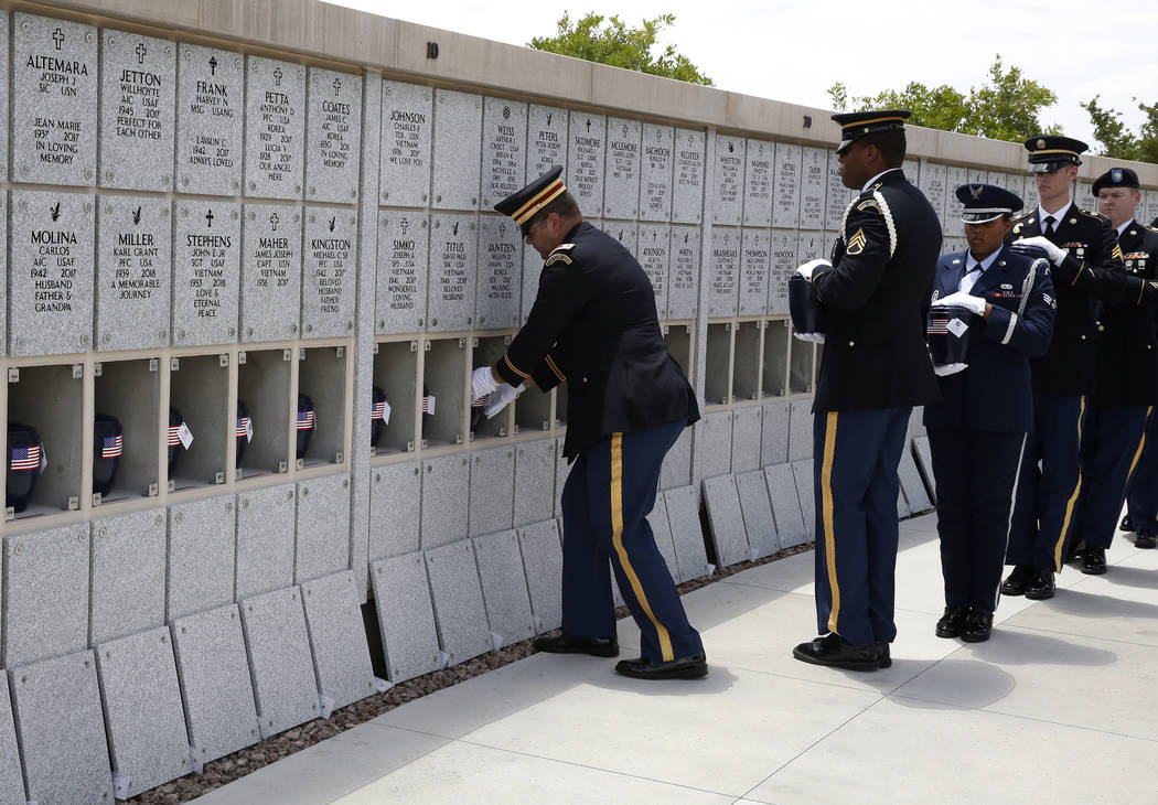 Nevada National Guard Capt. Howard Hoover, left, places unclaimed veteran remain into a wall during a military funeral service at the Southern Nevada Veterans Memorial Cemetery on Friday, June 15, ...