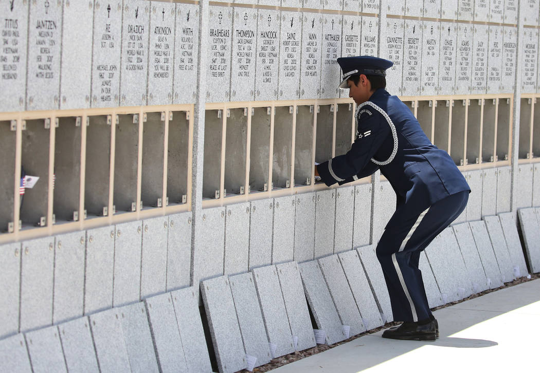 U.S. Air Force Airman 1st Class, Mary Jane Gutierrez, places unclaimed veteran remain into a wall during a military funeral service at the Southern Nevada Veterans Memorial Cemetery on Friday, Jun ...
