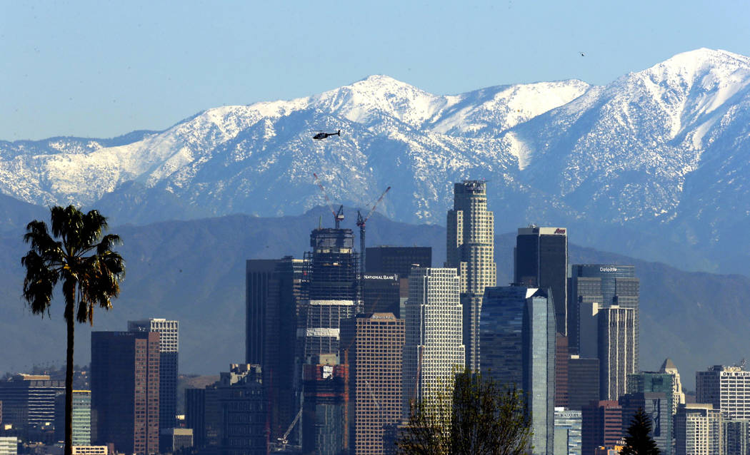 In this Jan. 12, 2016 file photo, the snow-capped San Gabriel Mountains stand as a backdrop to the downtown Los Angeles skyline. (AP Photo/Nick Ut, File)
