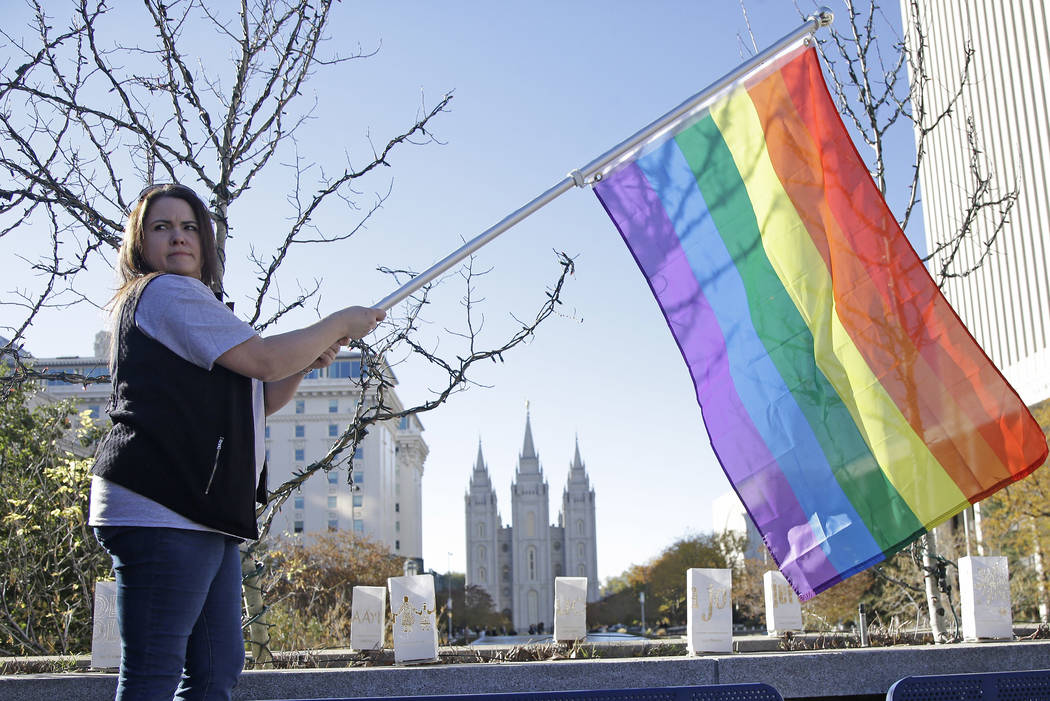Sandy Newcomb poses for a photograph with a rainbow flag as Mormons gather for a mass resignation from the Church of Jesus Christ of Latter-day Saints in Salt Lake City in 2015. (AP Photo/Rick Bowmer)