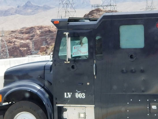 Matthew Wright holds up a sign during the standoff in the southbound lanes on the Mike O'Callaghan-Pat Tillman Bridge near the Hoover Dam on Friday. (Mark Mills via Twitter)