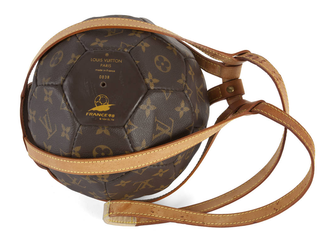 A limited edition monogrammed soccer ball with leather holder made by Louis Vuitton for the World Cup in France in 1998. Together with a copy of Rebonds, a limited edition Louis Vuitton coffee tab ...