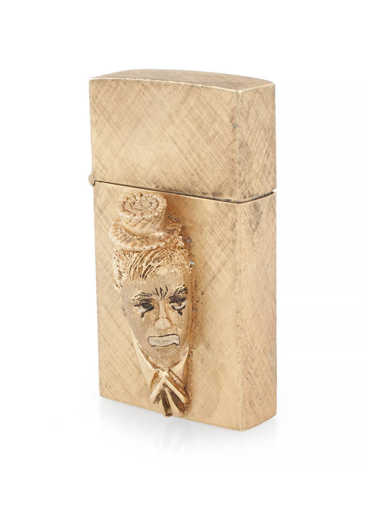 Offered for sale at the Julien's Jerry Lewis & Hollywood Legends Auction on Friday at Planet Hollywood: A 14-karat yellow gold lighter with satin finish, with a high relief caricature of Jerry Lew ...