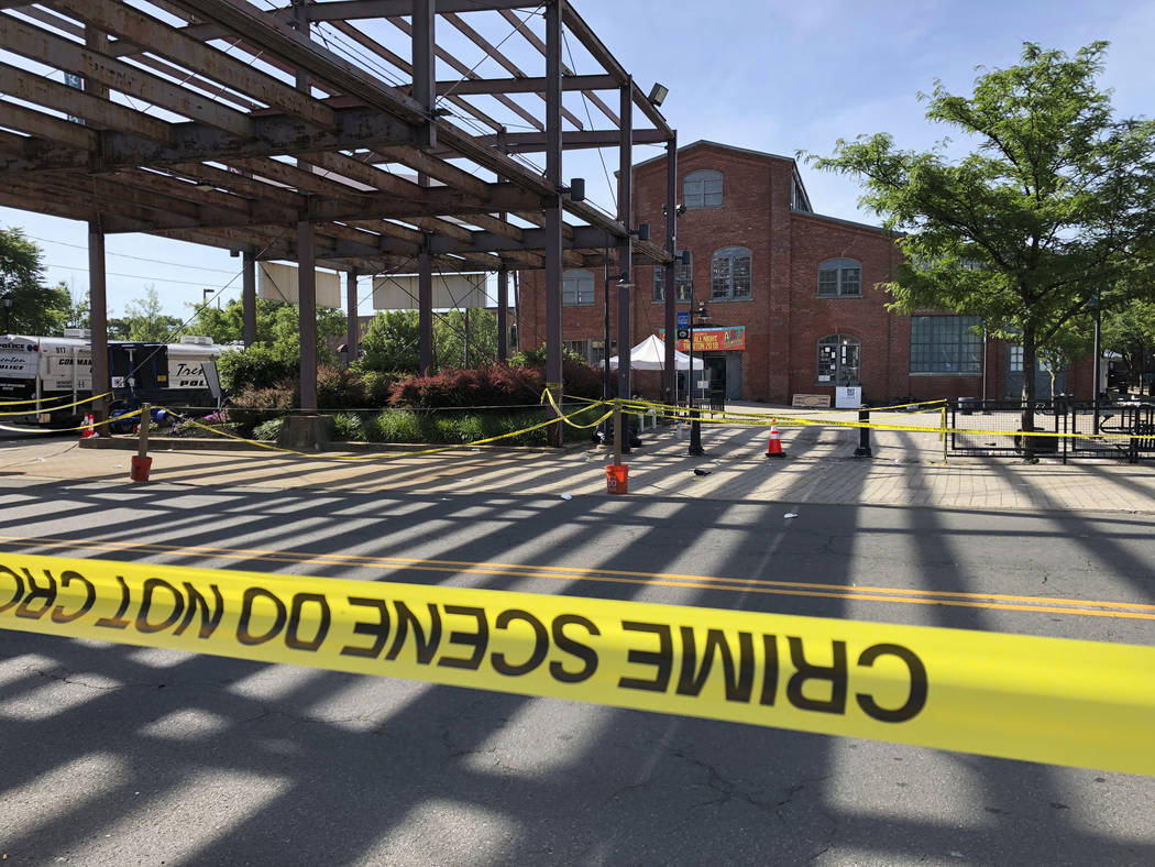Police crime-scene tape keeps people away from the brick Roebling Wire Works building, background, in Trenton, N.J., hours after a shooting broke out there at an all-night art festival early Sunda ...