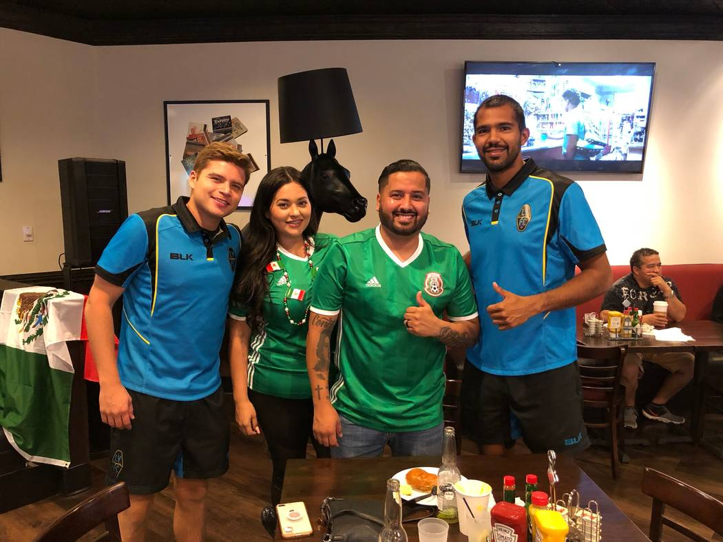 Lights FC midfielder Alex Mendoza, far left, and defender Miguel Garduno, far right, pose with fans at a watch party for Mexico's World Cup match against Germany on Sunday at the Plaza. (Lights FC)