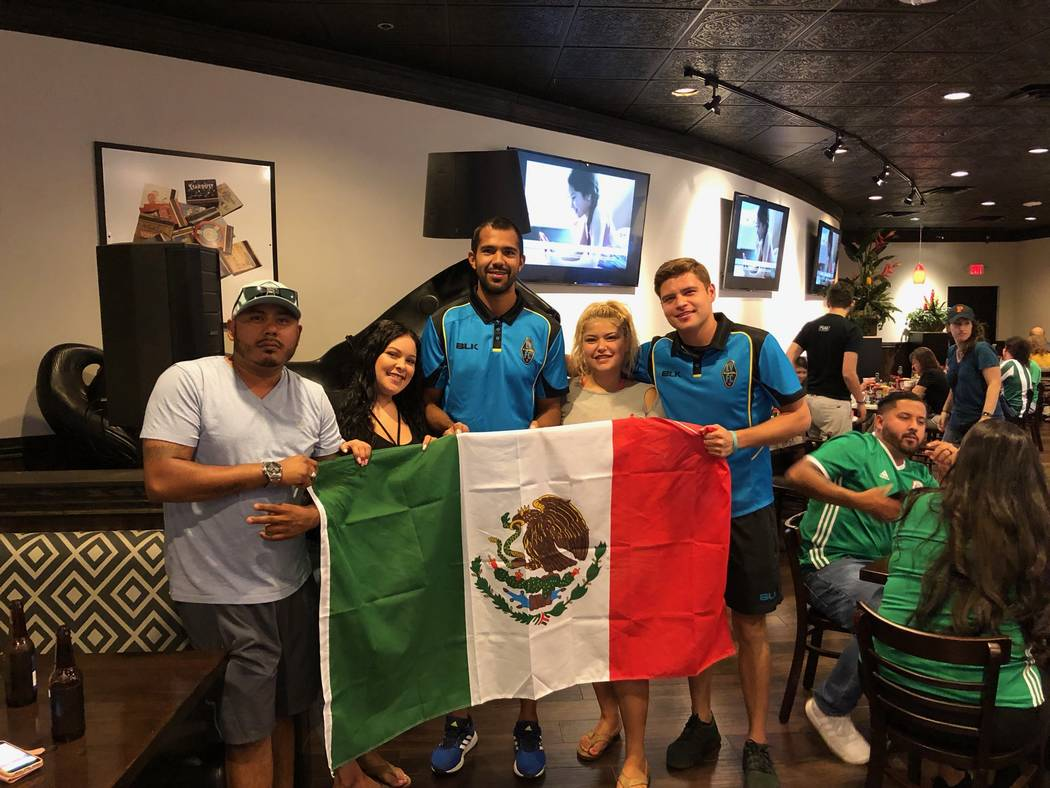 Lights FC defender Miguel Garduno, third from left, and midfielder Alex Mendoza, second from right, pose with fans at a watch party for Mexico's World Cup match against Germany on Sunday at the Pl ...
