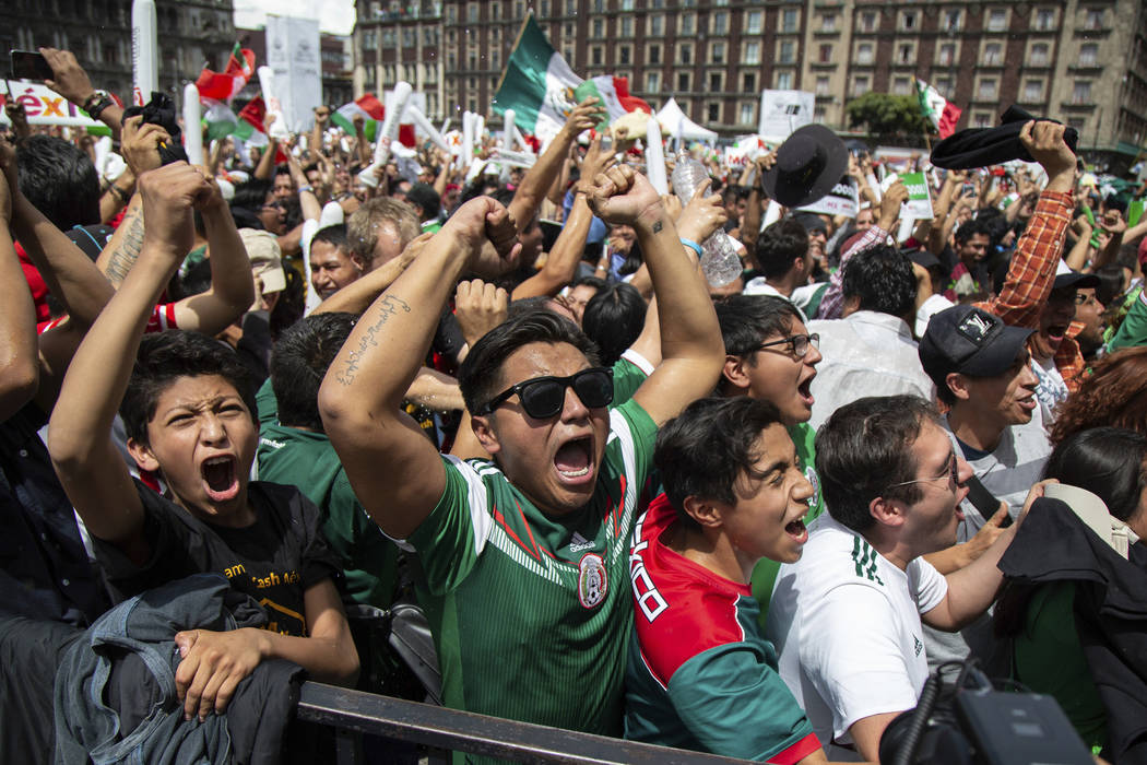 Fan's celebrate Mexico's win during the Mexico vs. Germany World Cup soccer match, as they watched it on an outdoor screen in Mexico City's Zocalo, Sunday, June 17, 2018. Mexico won it's first mat ...
