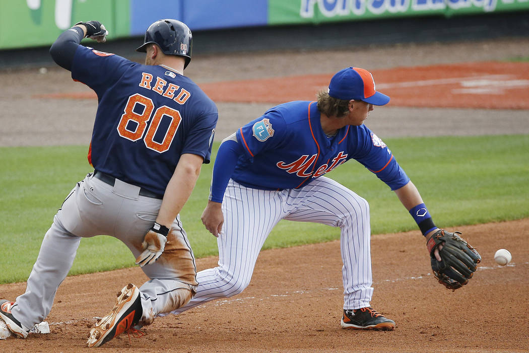 Houston Astros' A.J. Reed safely tags third base against New York Mets' Jeff McNeil during the seventh inning of a spring training baseball game, Thursday, March 24, 2016, in Port St. Lucie, Fla. ...