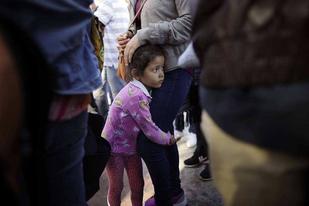 In this June 13, 2018 photo, Nicole Hernandez, of the Mexican state of Guerrero, holds on to her mother as they wait with other families to request political asylum in the United States, across th ...