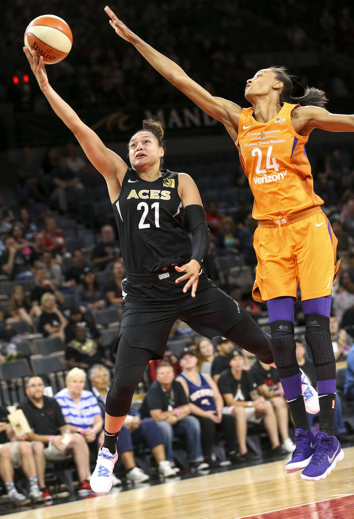 Las Vegas Aces guard Kayla McBride (21) takes a shot for a point over Phoenix Mercury forward DeWanna Bonner (24) during the first half of a WNBA basketball game at the Mandalay Bay Events Center ...
