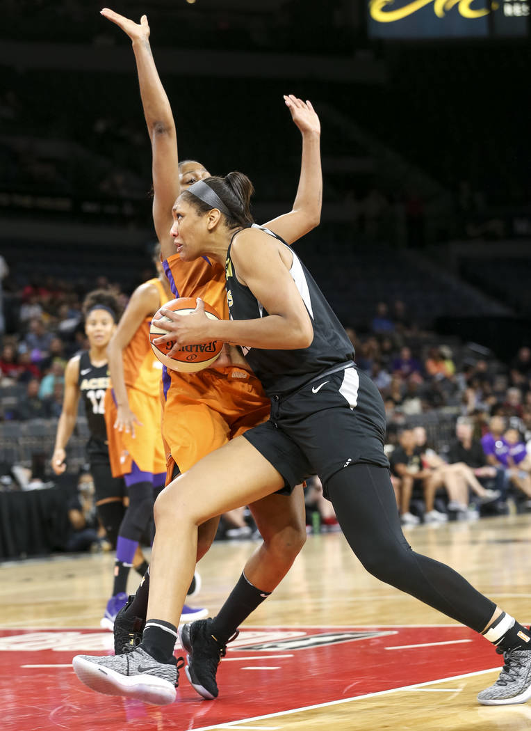 Las Vegas Aces center A'ja Wilson (22) drives the ball to the basket in front of Phoenix Mercury forward Camille Little (20) during the first half of a WNBA basketball game at the Mandalay Bay Eve ...