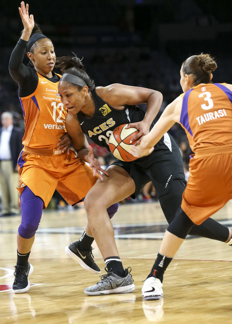 Las Vegas Aces center A'ja Wilson, center, finds an opening through Phoenix Mercury guards Briann January (12) and Diana Taurasi (3) during the second half of a WNBA basketball game at the Mandala ...