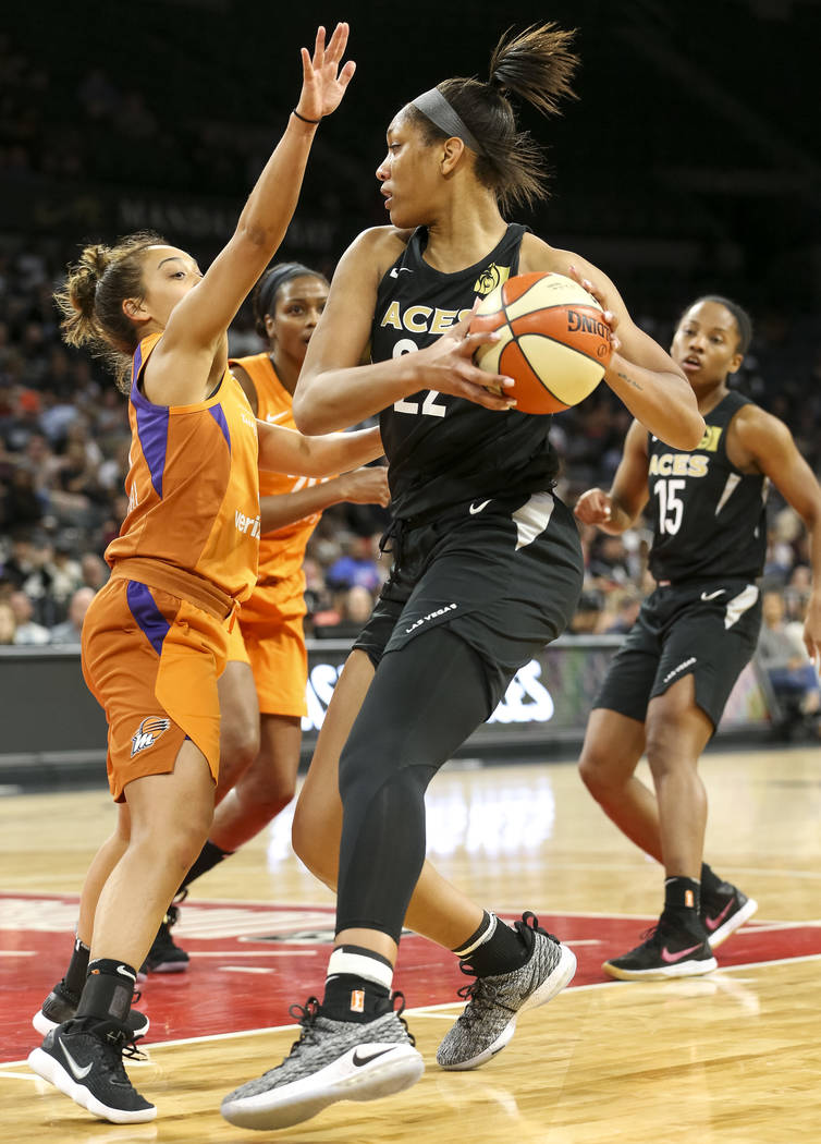 Las Vegas Aces center A'ja Wilson (22) looks to pass against Phoenix Mercury guard Leilani Mitchell (5) during the second half of a WNBA basketball game at the Mandalay Bay Events Center in Las Ve ...