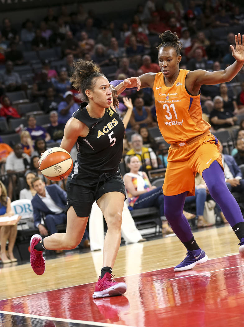 Las Vegas Aces forward Dearica Hamby (5) dribbles the ball past Phoenix Mercury forward Sancho Lyttle (31) during the second half of a WNBA basketball game at the Mandalay Bay Events Center in Las ...