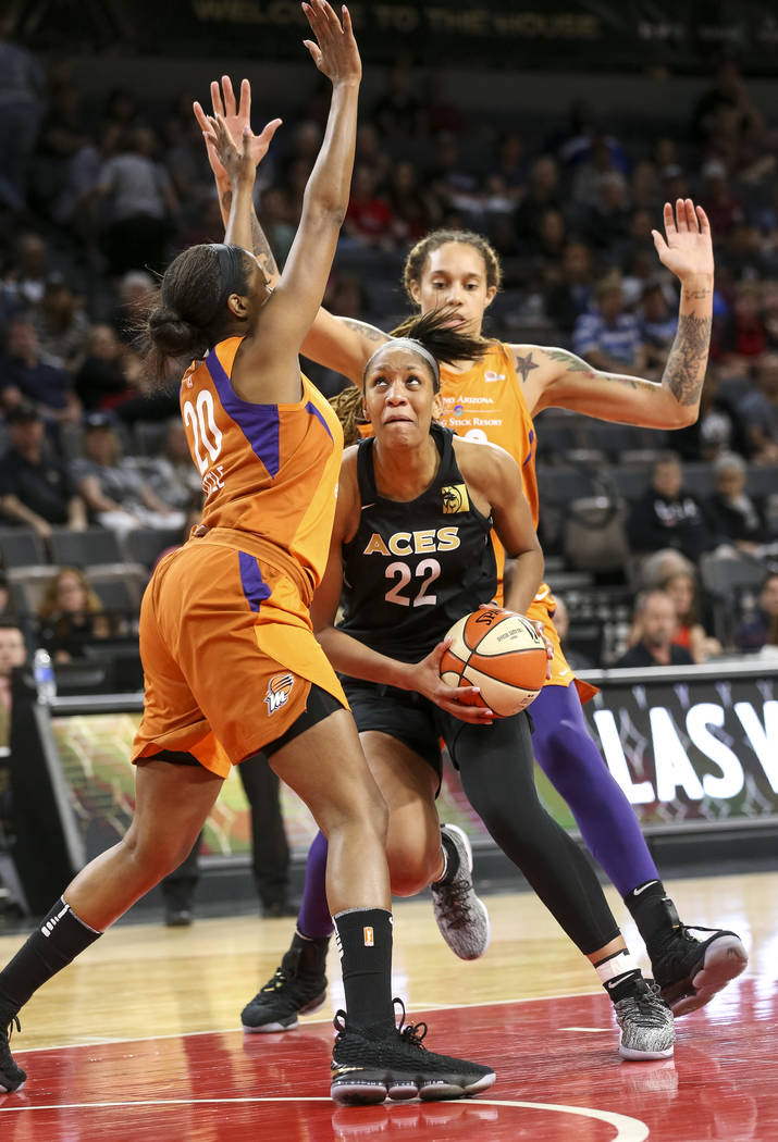 Las Vegas Aces center A'ja Wilson (22) looks for a shot against Phoenix Mercury forward Camille Little (20) and center Brittney Griner (42) during the second half of a WNBA basketball game at the ...