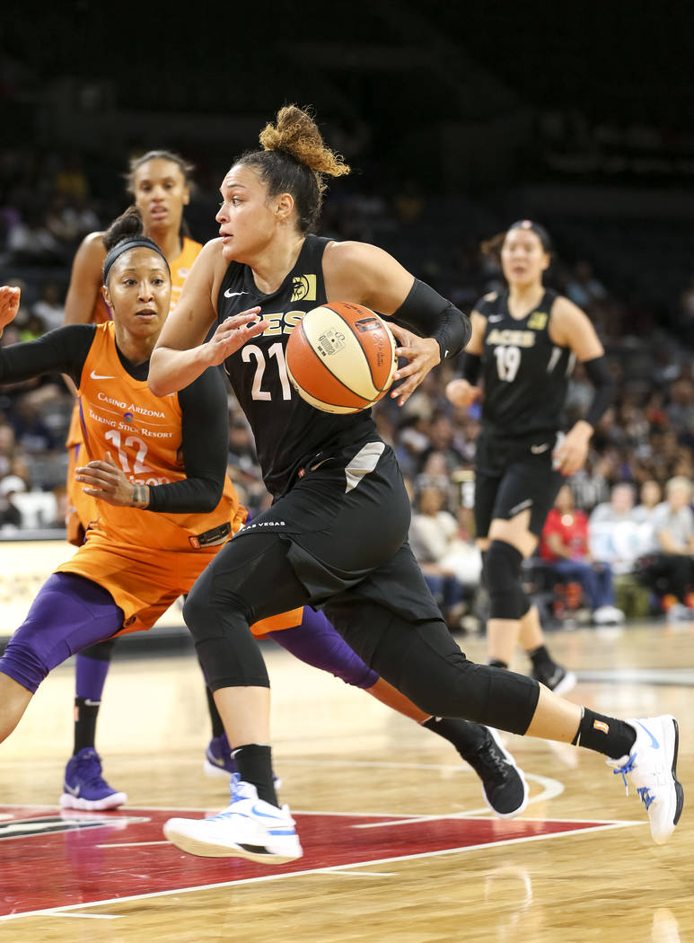 Las Vegas Aces guard Kayla McBride (21) drives the ball in front of Phoenix Mercury guard Briann January (12) during the second half of a WNBA basketball game at the Mandalay Bay Events Center in ...
