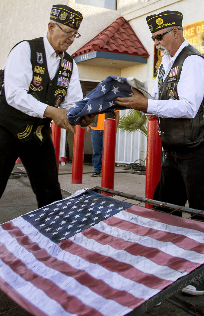 "Adjutant Victor ""Doc"" Moss, left, and Sergeant at Arms Paul Harris of the American Legion Post 149 lay out worn flags to be ceremoniously burned as part of Flag Day at the Leatherneck Cl ..."