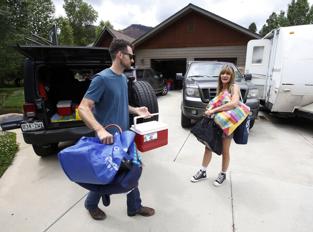 Andrew Korneoson helps his mother, Linda Korneoson, unload her car Sunday, June 17, 2018, as they move back into their home on County Road 203 in Hermosa, Colo. The family had been evacuated for 1 ...