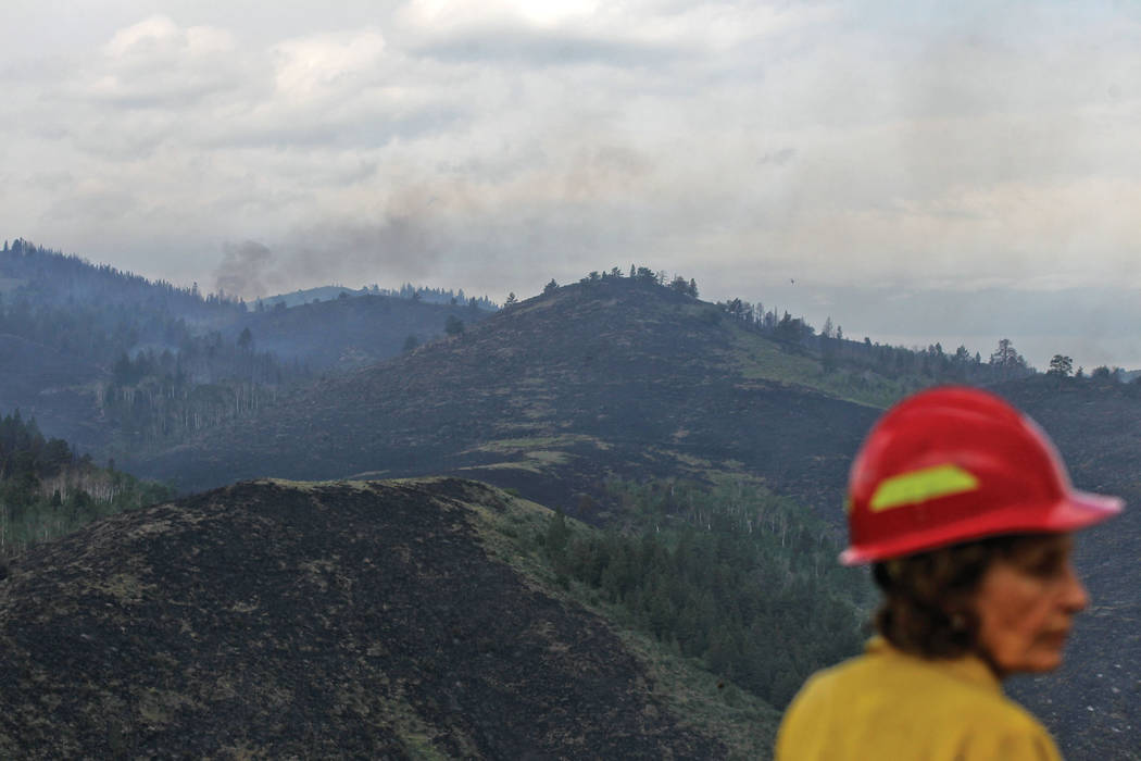 Rocky Mountain Black Team Fire Information Officer Lori Iverson looks away from a section of land affected by the Badger Creek Fire off Highway 10 near Jelm, Wyo., Saturday, June 16, 2018. (Shanno ...