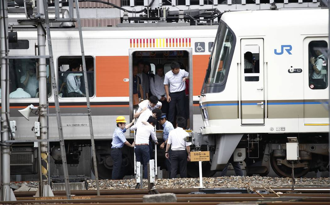 Passengers get off a train which suspended its service in Osaka, following an earthquake Monday, June 18, 2018. A strong earthquake shook the city of Osaka in western Japan on Monday morning, caus ...
