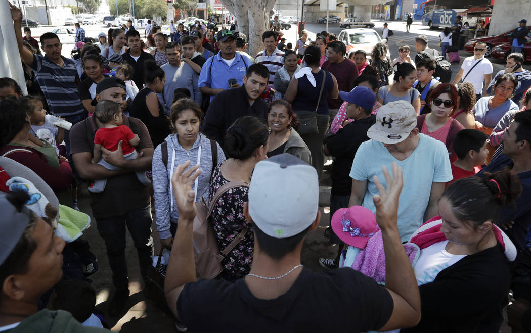 In this June 13, 2018 photo, an organizer, foreground, speaks to families as they wait to request political asylum in the United States, across the border in Tijuana, Mexico. In Tijuana, Latin Ame ...