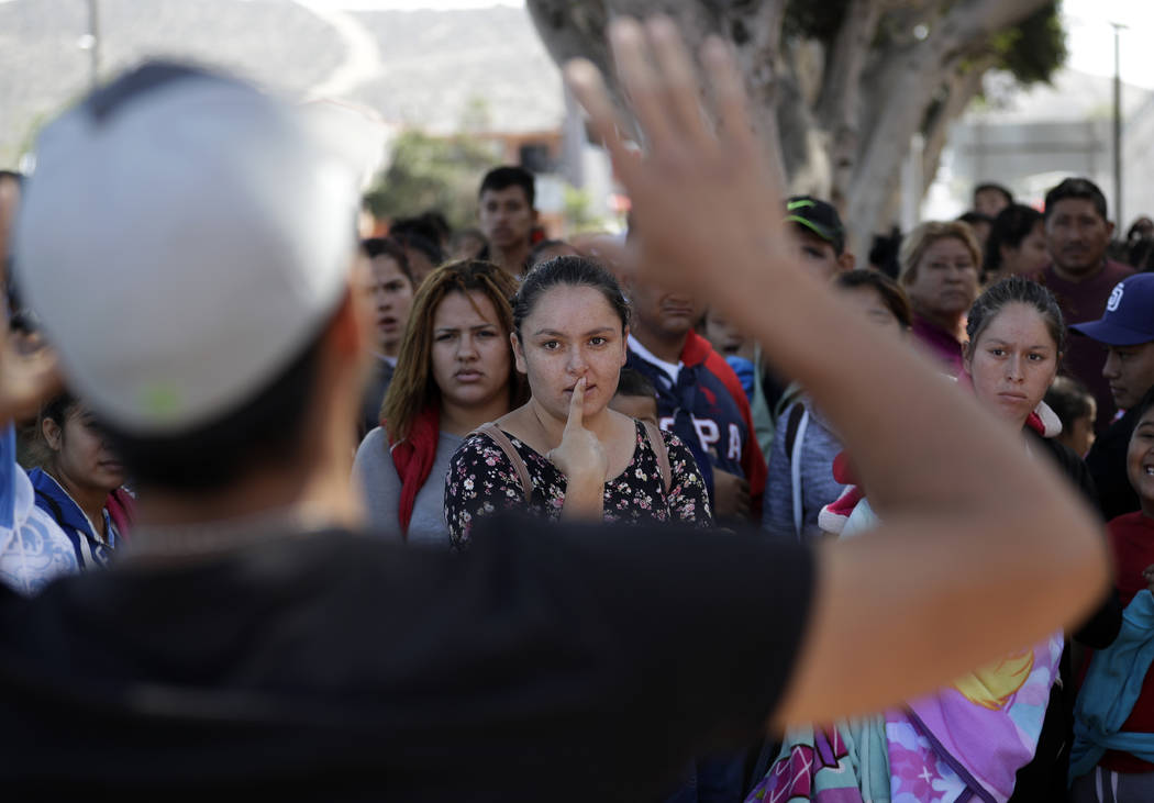 In this June 13, 2018 photo, an organizer speaks to families as they wait to request political asylum in the United States, across the border in Tijuana, Mexico. In Tijuana, Latin Americans fleein ...