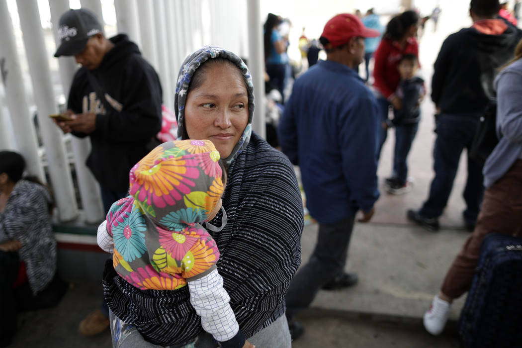 In this June 13, 2018 photo, Maria Rafaela Blancante, of the Mexican state of Michoacan, holds her daughter, Jazmin, as they wait with other families to request political asylum in the United Stat ...