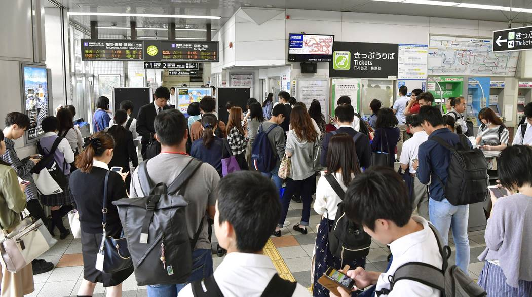 People wait for the resumption of train service which was suspended following an earthquake, at Nijo station, Kyoto, western Japan, Monday, June 18, 2018. A strong earthquake has shaken the city ...