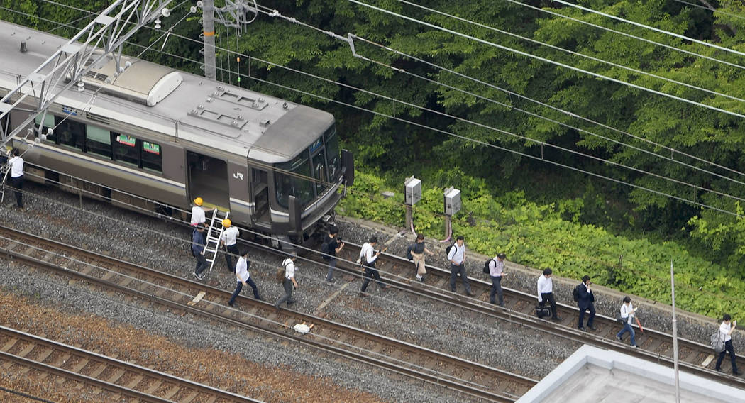 Passengers walk on railroad as the train service was suspended following an earthquake in Takatsuki, Osaka, Monday, June 18, 2018. A strong earthquake shook the city of Osaka in western Japan on ...