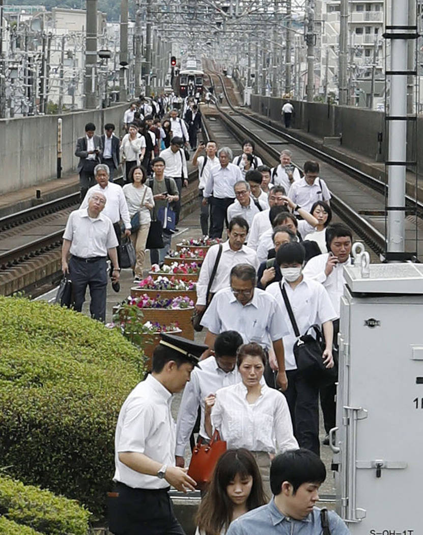 Passengers walk on railroad as train service was suspended following an earthquake in Ikeda, Osaka, Monday, June 18, 2018. A strong earthquake shook the city of Osaka in western Japan on Monday mo ...