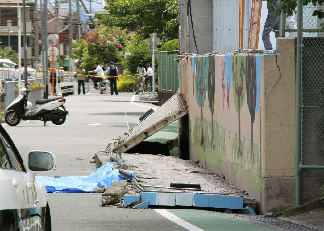 Wall lies on road after it fell down following an earthquake near an elementary school in Takatsuki, Osaka, Monday, June 18, 2018. A strong earthquake knocked over walls and set off scattered fire ...