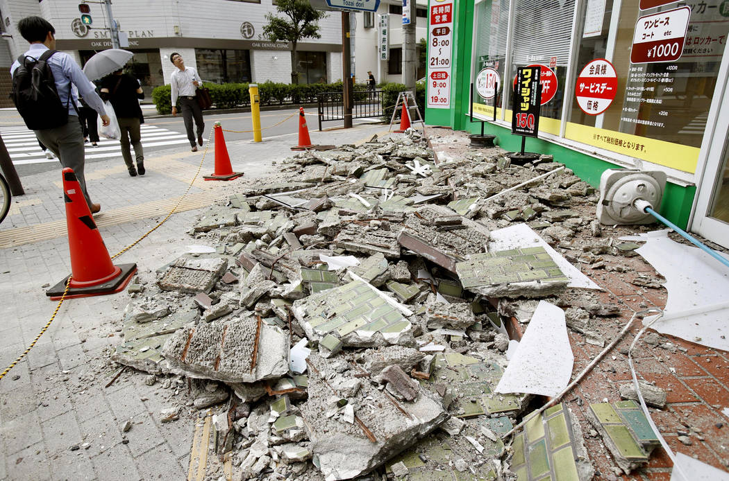 Debris of damaged walls are scattered following an earthquake, in Ibaraki, Osaka, Monday, June 18, 2018. A strong earthquake knocked over walls and set off scattered fires around the city of Osak ...