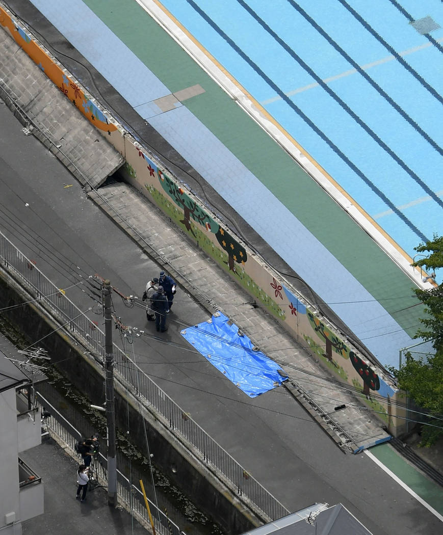 Police inspect the site, covered by blue sheet, where a girl was killed by fallen wall, following an earthquake near an elementary school in Takatsuki, Osaka, Monday, June 18, 2018. A strong earth ...
