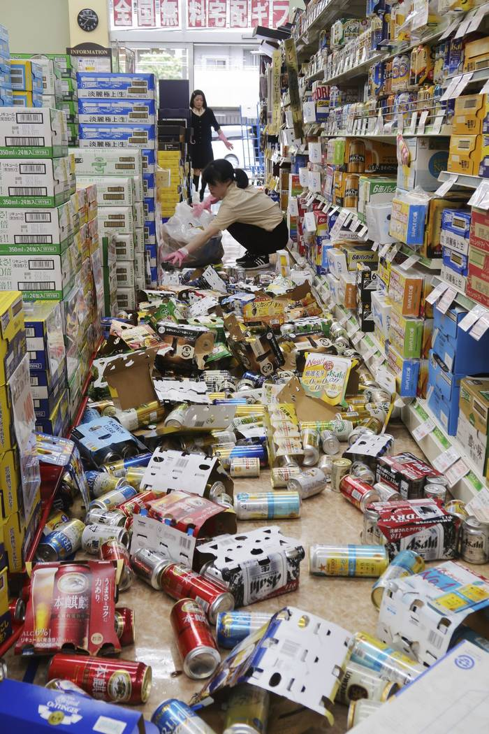Cans and other items litter the floor of a convenience store, following an earthquake in Hirakata, Osaka, Monday, June 18, 2018. A strong earthquake knocked over walls and set off scattered fires ...