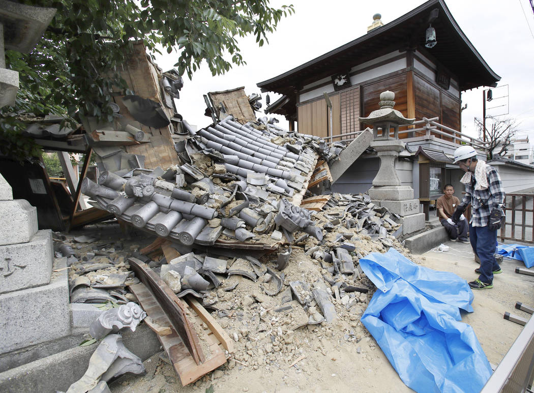 The gate of Myotoku-ji temple collapses after an earthquake hit Ibaraki City, Osaka, western Japan, Monday, June 18, 2018. A strong earthquake knocked over walls and set off scattered fires around ...