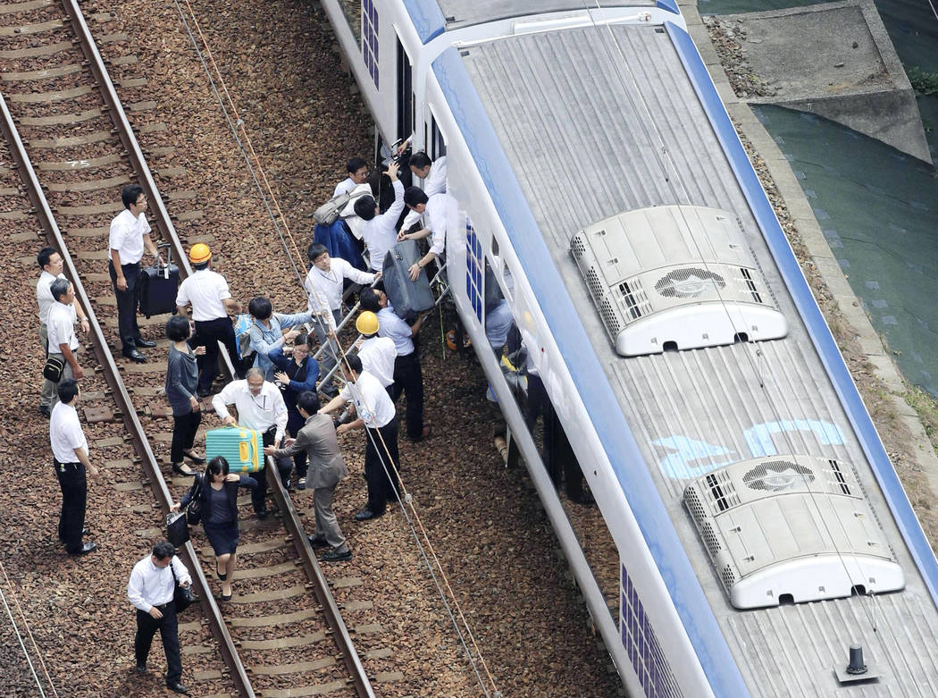 Passengers descend from a train on the track after train service was suspended to check for damage following an earthquake in Takatsuki city, Osaka, western Japan, Monday, June 18, 2018. A strong ...