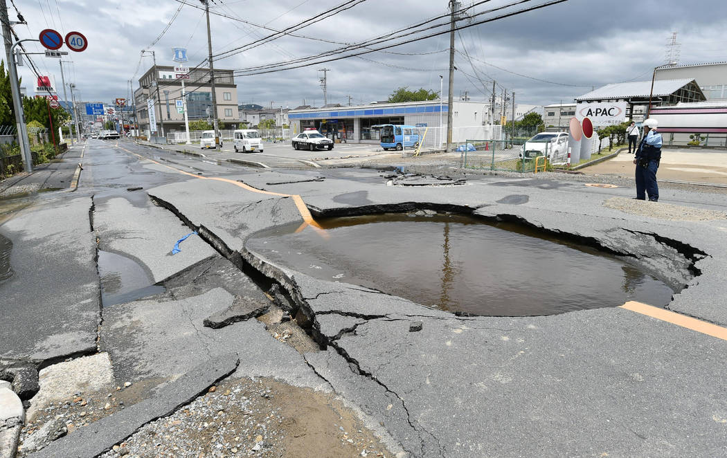 A crack is filled with water on a road after water pipes were broken following an earthquake in Takatsuki city, Osaka, western Japan, Monday, June 18, 2018. A strong earthquake knocked over walls ...