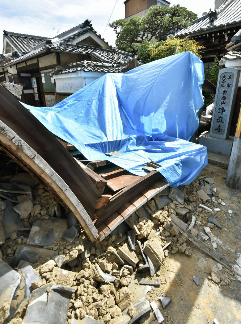 The gate of Jokyoji temple collapses after an earthquake in Ibaraki city, Osaka, western Japan, Monday, June 18, 2018. A strong earthquake knocked over walls and set off scattered fires around met ...