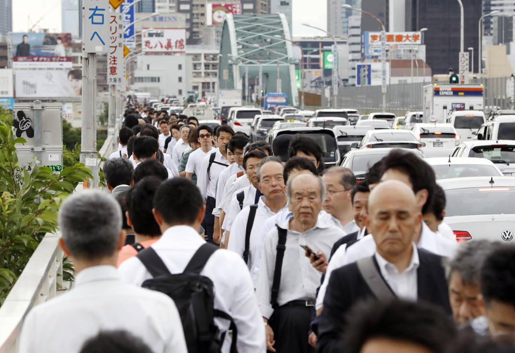 People walk on a bridge while train and subway service were suspended to check for damage after an earthquake in Osaka, western Japan, Monday, June 18, 2018. Dozens of flights were grounded, train ...