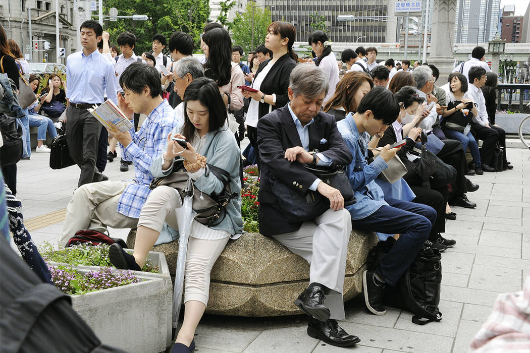 People wait for train service to resume following an earthquake in Osaka, Monday, June 16, 2018. A strong earthquake shook the city of Osaka in western Japan on Monday morning, causing scattered d ...