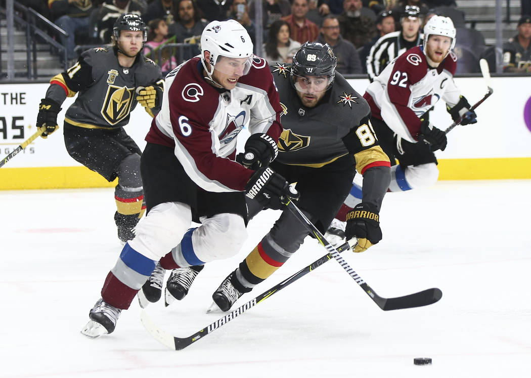 Golden Knights right wing Alex Tuch (89) tries to get the puck from Colorado Avalanche defenseman Erik Johnson (6) during the third period of an NHL hockey game at T-Mobile Arena in Las Vegas on M ...