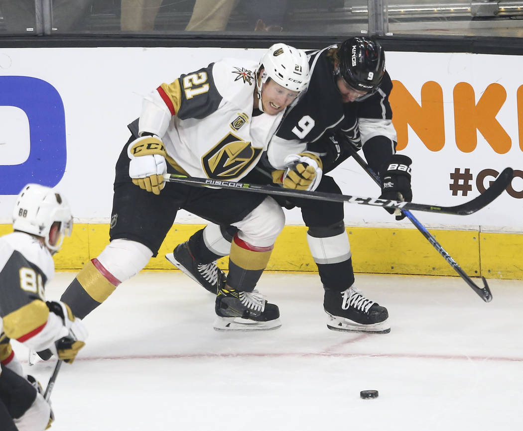 Golden Knights center Cody Eakin (21) and Los Angeles Kings left wing Adrian Kempe (9) battle for the puck during the first period of Game 4 of an NHL hockey first-round playoff series at the Stap ...
