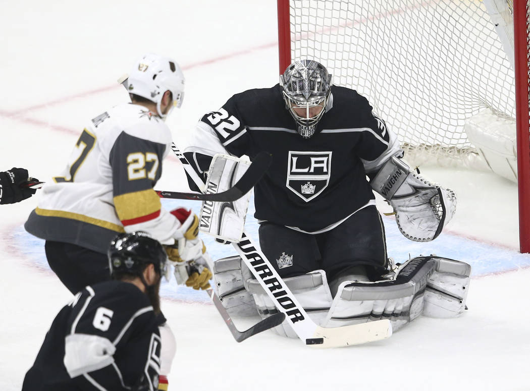 Los Angeles Kings goaltender Jonathan Quick (32) blocks a shot as Golden Knights defenseman Shea Theodore (27) goes for the puck during the first period of Game 4 of an NHL hockey first-round play ...