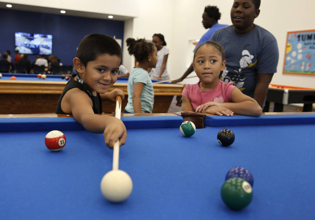 """Armani Valenzuela, 5, plays billiard pool as his friend Sariya Jonson Milton, 6, looks on during """"Meet Up to Eat Up"""" program at the Boys and Girls Club at 3475 S. Mountain Vista St. on T ..."""