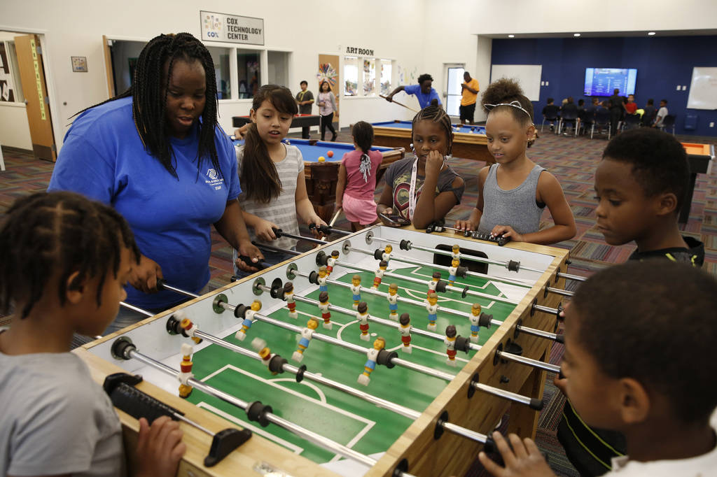 """Danielle Reed, left, Summer Program leader, plays table soccer with children, including, Halo Frank, 7, left, and Jocelyn Delgadillo, 8, third left, during """"Meet Up to Eat Up"""" program at ..."""