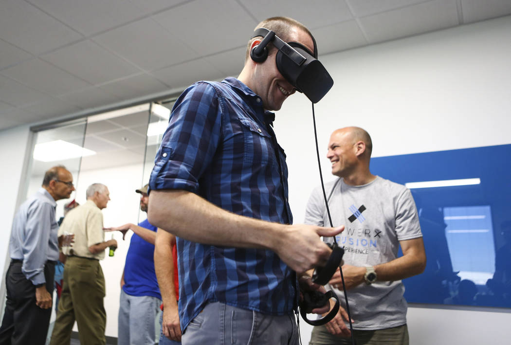 Barron Stone, left, picks up items using a virtual reality headset with the help of MSgt. Powell Crider, right, at the grand debut of the completed Innovation Center and Prototyping Lab at AFWERX ...